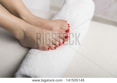 Foot with red gel pedicure on white towel