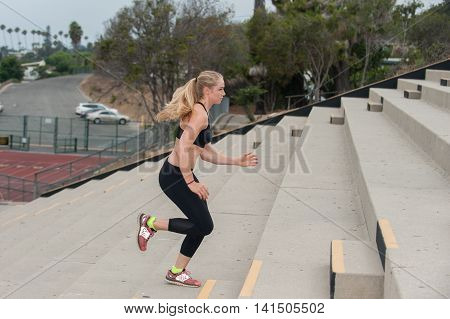 Athlete in black tights training on concrete steps.