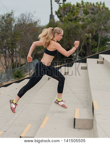 Athlete in black tights leaping up concrete steps.