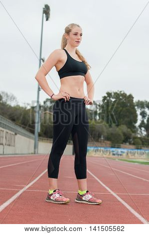 Female blond track runner in black tights standing with confidence.