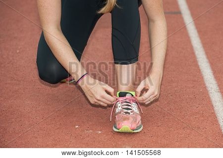 Female hands, legs in black tights, tying shoes on track.