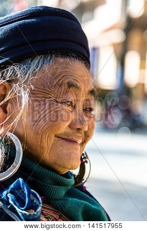Sapa Lao Cai Province Vietnam - November 25 2014: Hmong old woman at a market and wearing traditional attire in Sapa town on November 25 2014 Lao Cai Province North Vietnam.