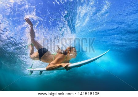 Young active girl in bikini in action - surfer with surf board dive underwater under breaking big ocean wave. Family lifestyle people water sport adventure camp beach extreme swim on summer vacation