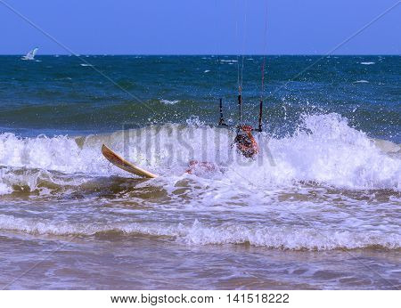 Man kite surfer in action over wavy sea surface, outdoor activity on tropical summer vacations