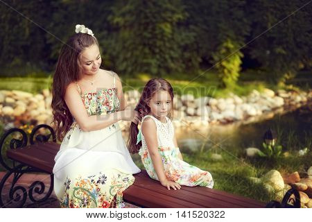 Beautiful white European woman combing long hair of his daughter sitting outdoors near the pond. Nice girl sits quietly and loves his mother
