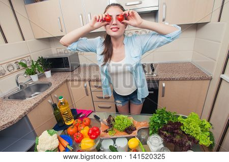 Young girl having fun in the kitchen . Tomatoes instead of eyes . It is very fun . Home kitchen.Wide angle