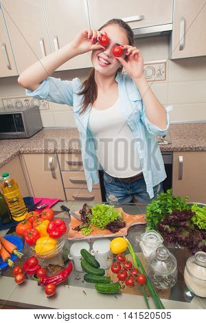 Young girl having fun in the kitchen . Tomatoes instead of eyes . It is very fun . Home kitchen. Wide angle