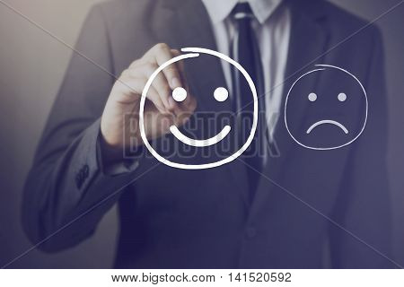 Customer Choosing To Write Satisfied Face Over Unhappy Face