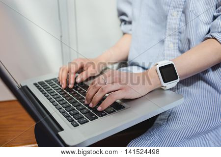 Mid section of woman using laptop in locker room