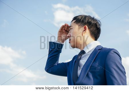 Asian Business Man Searching Or Looking For Opportunity Over Blue Sky Background