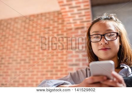 Young woman listening song and using mobile phone in locker room