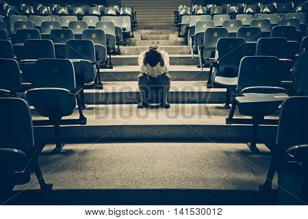 Businessman sitting desperately in the middle of the stair path with rows of chairs along both sides
