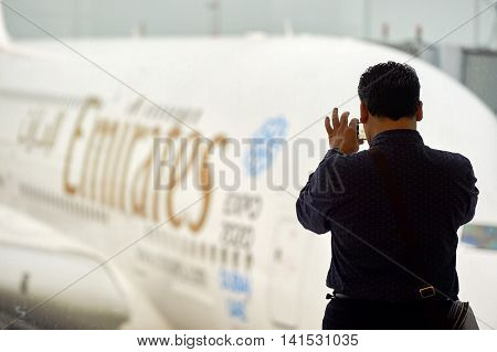 HONG KONG - MARCH 09, 2015: a man taking photo of docked Airbus A380. The Airbus A380 is a double-deck, wide-body, four-engine jet airliner.