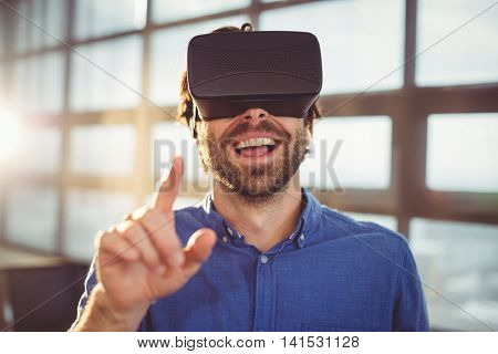 Male business executive using virtual reality headset in office