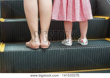Mother and a young female kid on a moving escalator / Do not let a child go alone on an escalator concept
