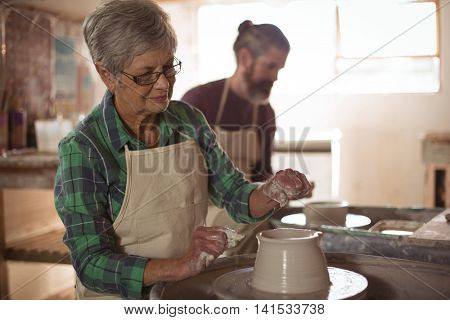Female potter making a pot in pottery workshop