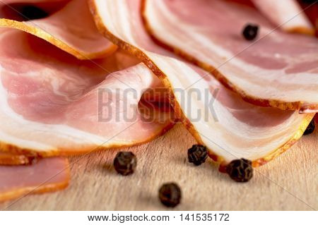 Slices Of Pink Bacon With Black Peppercorn On Wooden Board