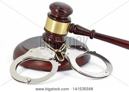 Wooden gavel and handcuffs isolated on white background