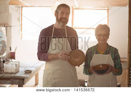 Male and female potter holding earthenware pots in pottery workshop