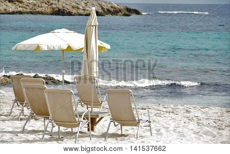 chairs deck chairs and parasols on the shore of the blue sea