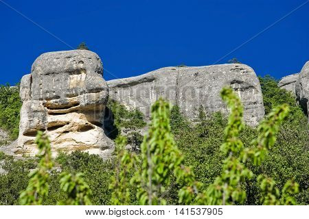 stone cliffs like faces with blue sky