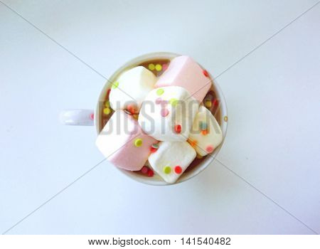 Cup of coffe with marshmallows in confetti