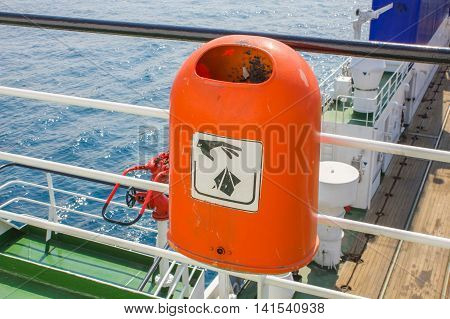 Red plastic rubbish bin with a sign hand throw garbage on the ship against the blue sea