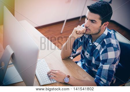 Handsome businessman in casual cloth sitting at the table and using personal computer in office