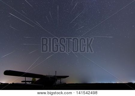 Meteor Shower. Falling stars. Meteor Shower starry night. Perseid meteor shower. Real night sky, Starry night. Light pollution. Silhouette of airplane. Composite Photo of Perseid meteor activity