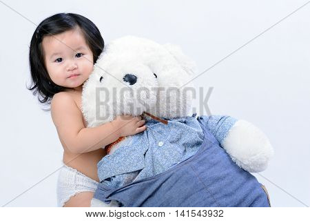 Adorable little asian girl hugging a teddy bear on white background