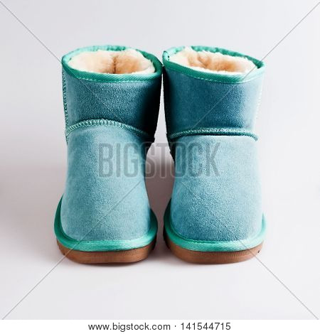 female blue winter shoes in grey background