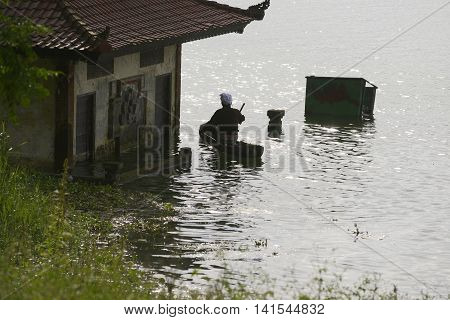 Silhouette of a man paddling toward a lakeside houses submerged in water at Lake Batur Bali Indonesia