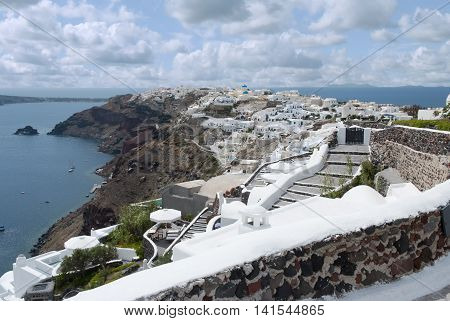 Oia town on Santorini island Greece. Traditional and famous white houses and churches with blue domes over the Caldera Aegean sea