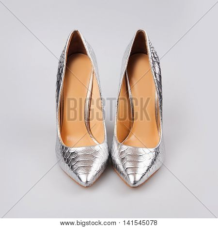 Silver high heels pump shoes over grey