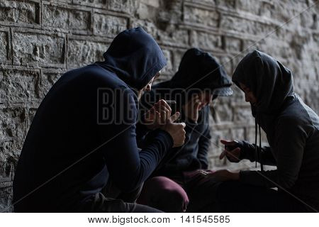 substance abuse, addiction and bad habits concept - close up of young people smoking cigarettes outdoors