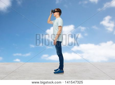 3d technology, virtual reality, entertainment, cyberspace and people concept - happy young man with virtual reality headset or 3d glasses looking at something over blue sky and clouds background