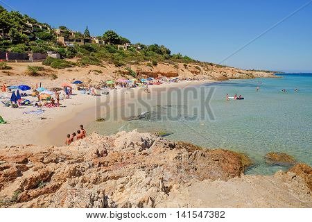 View on the beach with sand and cliffs. Pinus Village in Sardinia Italy.02.08.2016.
