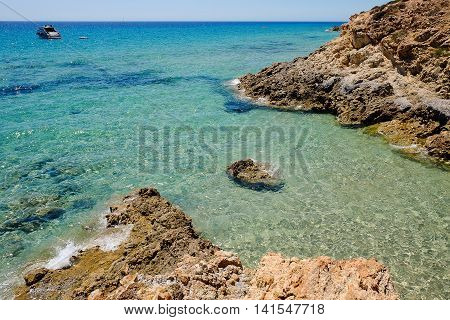 Beach Pinus Village with rock and a boat in blue sea.
