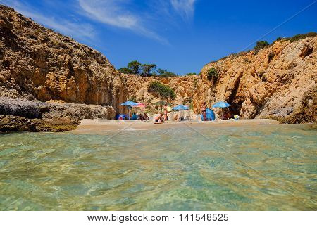 Small beach between the rocks with colorful sun umbrellas and an unknown people. Pinus Village in Sardinia Italy.02.08.2016.