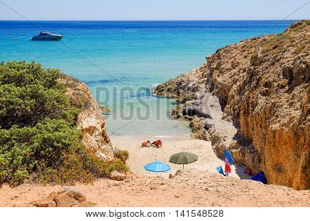 Beach with two persons playing on the sand and a boat in the sea. Pinus Village in Sardinia Italy.02.08.2016.