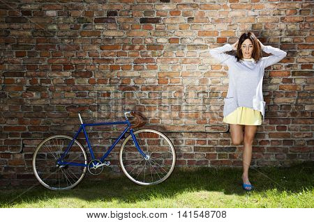 Young Woman And Old Blue Bike