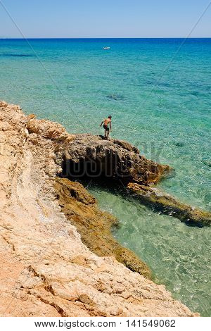 Man on a cliff going to jump into the emerald sea water in Sardinia. Pinus Village in Sardinia Italy.02.08.2016