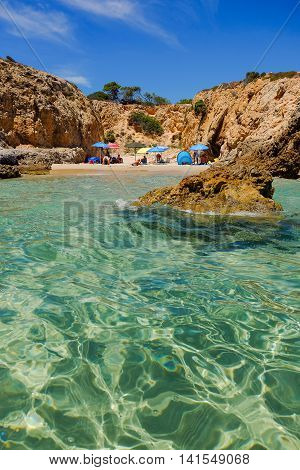 Small beach between the rocks with colorful sun umbrellas and an unknown persons. Pinus Village in Sardinia Italy.02.08.2016