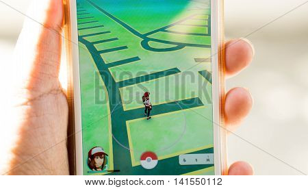 Rayong, Thailand - August 7, 2016: A woman holds a mobile phone with pokemon go app with a young woman character. free game developed by Niantic for iOS and Android devices with sunlight-select focus