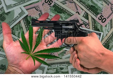 marijuana and gun in his hands on the dollars background