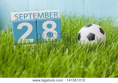 September 28th. Day 28 of month, wooden color calendar on green grass lawn background. Autumn time. Empty space for text.