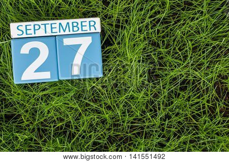 September 27th. Day 27 of month, wooden color calendar on green grass lawn background. Autumn time. Empty space for text.