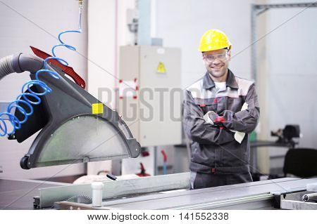 Worker at CNC machine shop with lathes
