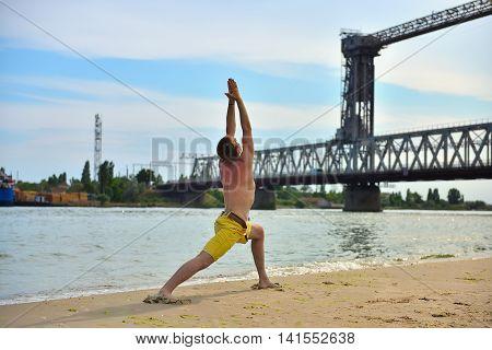 man making yoga exercises on harbor crane background