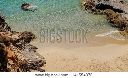 Emerald crystal sea water with small waves mooving on the sand on a small beach between two rocks in Pinus Village Sardinia Italy.